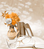 Vaso com flores, livros azuis, vidros, livros abertos na luz - fundo azul Cartão da educação Foto de Stock Royalty Free
