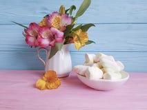 Vaso com o marshmallow de madeira do fundo do alstroemeria, doçura Imagens de Stock