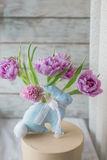 Vaso com um ramalhete das tulipas e de um coelho de uma tela Imagem de Stock