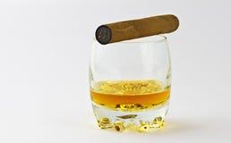 Vaso con el whisky y un cigarro foto de archivo