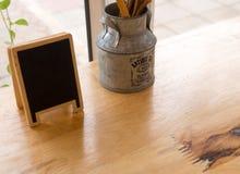 Vaso con ferro e sei numeri fatti da stile di legno e d'annata sulla tavola in caffetterie Fotografia Stock