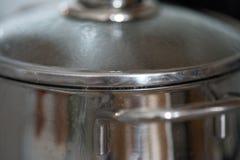 Vaso con il coperchio, acqua lanciante che cucina grano saraceno Immagine Stock