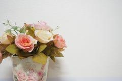 Vaso con il fondo bianco della parete delle rose immagine stock