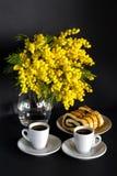 Vaso con la mimosa, due tazze di caffè e lo strudel del seme di papavero su un fondo nero Fotografia Stock