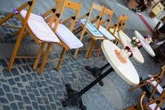Vaso con la tavola bianca dei fiori in del caffè via all'aperto Immagine Stock Libera da Diritti