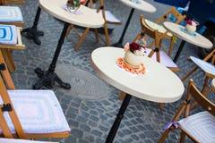 Vaso con la tavola bianca dei fiori in del caffè via all'aperto Fotografie Stock