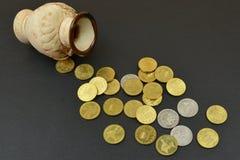 Vaso con le monete sulla tavola con fondo nero Immagine Stock Libera da Diritti