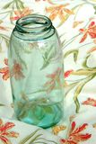 Vaso d'inscatolamento dell'annata della nonna su un tovagliolo di piatto floreale Immagini Stock Libere da Diritti