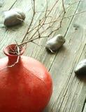Vaso da argila vermelha com galhos e as pedras secos em de madeira Fotografia de Stock Royalty Free