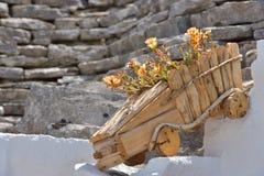 Vaso da fiori di legno con la vecchia casa di pietra esteriore del flowerson variopinto Fotografia Stock Libera da Diritti