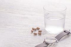 Vaso de agua de Misted y cápsulas médicas marrones en una tabla de madera vieja blanca Ciérrese para arriba en un fondo blanco foto de archivo
