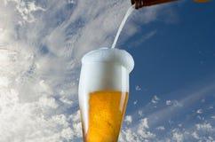 Vaso de cerveza de colada de la botella en fondo del cielo azul imágenes de archivo libres de regalías