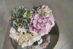 Vaso de flores coloridas na tabela do espelho com assoalho de madeira Imagem de Stock