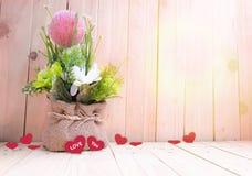 Vaso de flores com corações na tabela de madeira, fundo do dia do ` s do Valentim Fotos de Stock Royalty Free