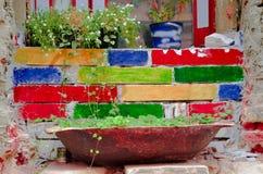 Vaso de flores das flores que estão em uma soleira Imagens de Stock Royalty Free