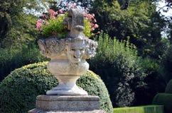Vaso de flores histórico com a estátua da cabeça humana no jardim do castelo Imagens de Stock Royalty Free