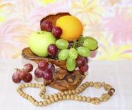 Vaso de madeira com maçãs, uvas e laranjas Fotos de Stock