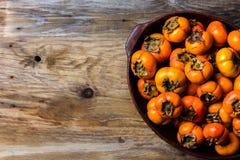 Vaso del cachi del cachi di frutta fresca su fondo di legno Copi lo spazio Immagini Stock