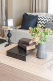 Vaso del fiore con i libri sulla tavola di legno in salone Fotografia Stock