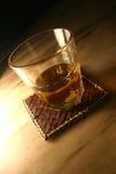 Vaso del whisky en la estera Imagen de archivo
