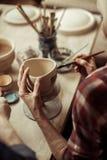 Vaso di argilla della pittura della donna all'officina Fotografia Stock