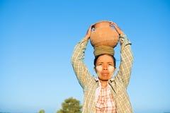 Vaso di argilla di trasporto dell'agricoltore femminile tradizionale asiatico maturo sulla testa Immagini Stock