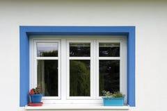Vaso di fiore blu con i fiori rossi sul davanzale bianco della finestra della finestra blu Fotografie Stock