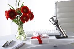 Vaso di fiore e del presente sulla tavola dell'ufficio Immagini Stock Libere da Diritti