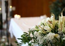 Vaso di molti fiori su un altare nella chiesa e nelle candele Fotografia Stock