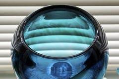 Vaso di vetro blu contro i ciechi immagine stock