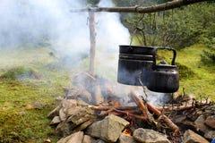 Vaso e bollitore sopra il fuoco di accampamento Immagine Stock