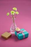 Vaso e queque de flor com as caixas de presente contra o fundo cor-de-rosa Foto de Stock Royalty Free