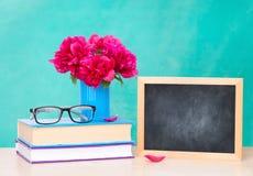 Vaso em uma pilha dos livros e um quadro de madeira para escrever em uma tabela, o dia do conhecimento imagem de stock