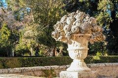 Vaso esculpido com fruto como a decoração em um jardim Imagens de Stock