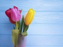 Vaso fresco das tulipas bonitas, aniversário bonito em um fundo de madeira azul Fotografia de Stock