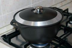 Vaso nero del metallo coperto di coperchio sulla stufa di gas Fotografia Stock