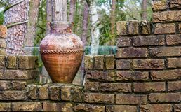Vaso romano lascado velho em uma parede de tijolo, em umas decorações exteriores do jardim e em uma arquitetura foto de stock royalty free