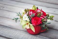Vaso vermelho pequeno com o ramalhete das flores e dos lírios no espaço de madeira da tabela para o texto Imagem de Stock