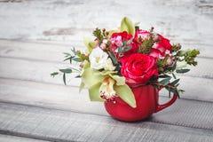 Vaso vermelho pequeno com o ramalhete das flores e dos lírios no espaço de madeira da tabela para o texto Foto de Stock