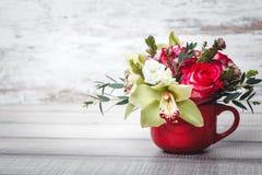 Vaso vermelho pequeno com o ramalhete das flores e dos lírios no espaço de madeira da tabela para o texto Fotografia de Stock