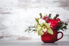 Vaso vermelho pequeno com o ramalhete das flores e dos lírios no espaço de madeira da tabela para o texto Fotos de Stock