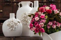Vasos brancos decorativos diferentes no fundo de Brown Imagem de Stock Royalty Free