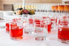 Vasos con las bebidas rojas y descoloridas en el evento corporativo imagen de archivo