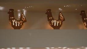 Vasos da argila sob a forma dos galos na prateleira A vela está queimando-se para dentro interior e conforto da casa vídeos de arquivo