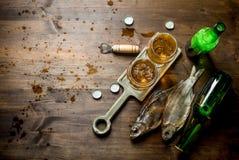 Vasos de cerveza en un soporte y un pescado secado fotografía de archivo libre de regalías