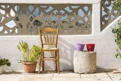 Vasos de flores e cadeira coloridos nas ruas de Karpathos, Greec Imagens de Stock Royalty Free