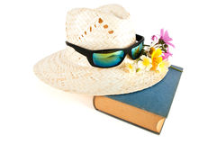 Vasshatt, solglasögon, blommor och bok Arkivfoto