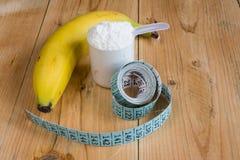 Vasslaprotein med att mäta bandet och bananen Arkivfoton