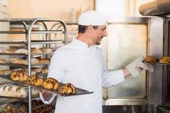 Vassoi sorridenti della tenuta del panettiere di croissant immagine stock