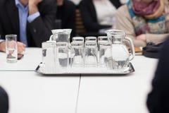 Vassoio con il lanciatore ed i bicchieri d'acqua Immagine Stock